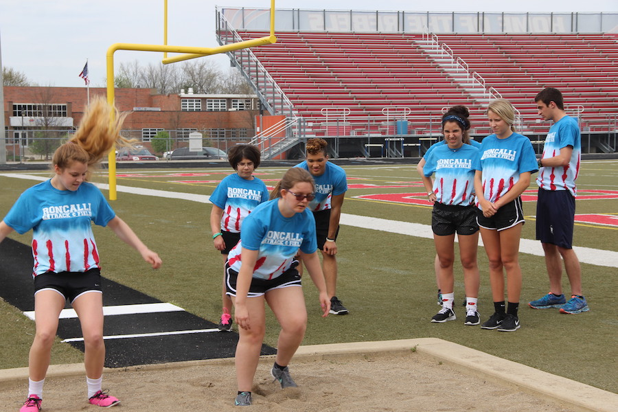 Sophomore Kelli Mariutto helps senior Katie Strange perfect the track event long jump at a practice at Roncalli High School.  The team will have three home meets during the 2017 season.