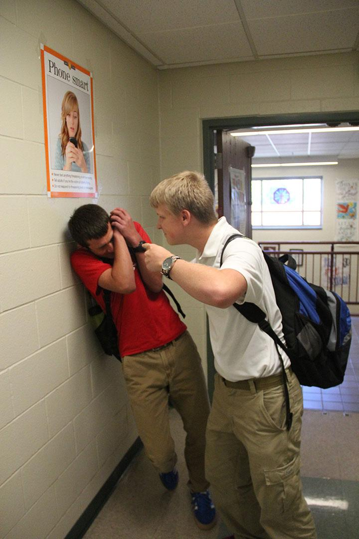 """Junior Chris Golab holds sophomore Adam Wolf up to a wall for trying to use the """"junior hallway"""". A select few juniors have known to torture underclassman because of their major misconception that there actually is a """"junior hallway""""."""