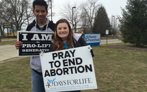 REPPING THEIR CLUB: Seniors Micah Attai and Courtney Smith pray outside of Planned Parenthood. The club has seen a recent decline in membership compared to years prior.
