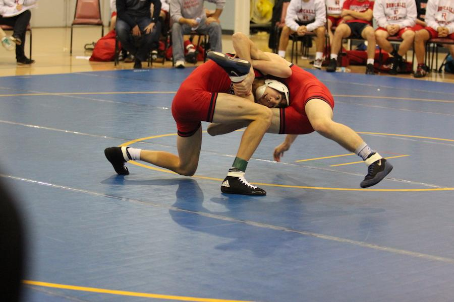TOUGH COMPETITOR: Alec Viduya uses all his effort to try to pin Jarrod Shanley to the ground. Viduya competed at a meet held at Roncalli.