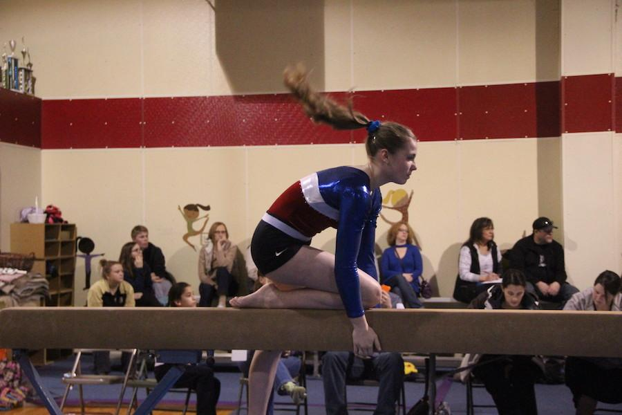 BEAMING PERFORMANCE: Junior Kayleigh Winter does a routine on the balance beam. Winter feels the gymnastics team has greatly bonded this season.