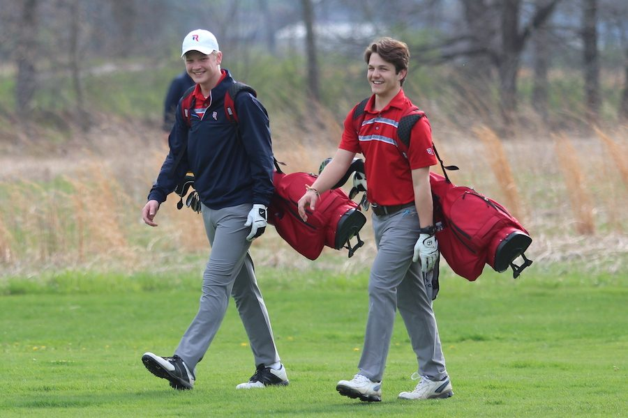 ON+THE+GREEN%3A+Sophomore+Zachary+Schott+and+junior+Jack+Baker+walk+to+their+ball+after+tee+off.+The+golf+season+began+on+April+11th.