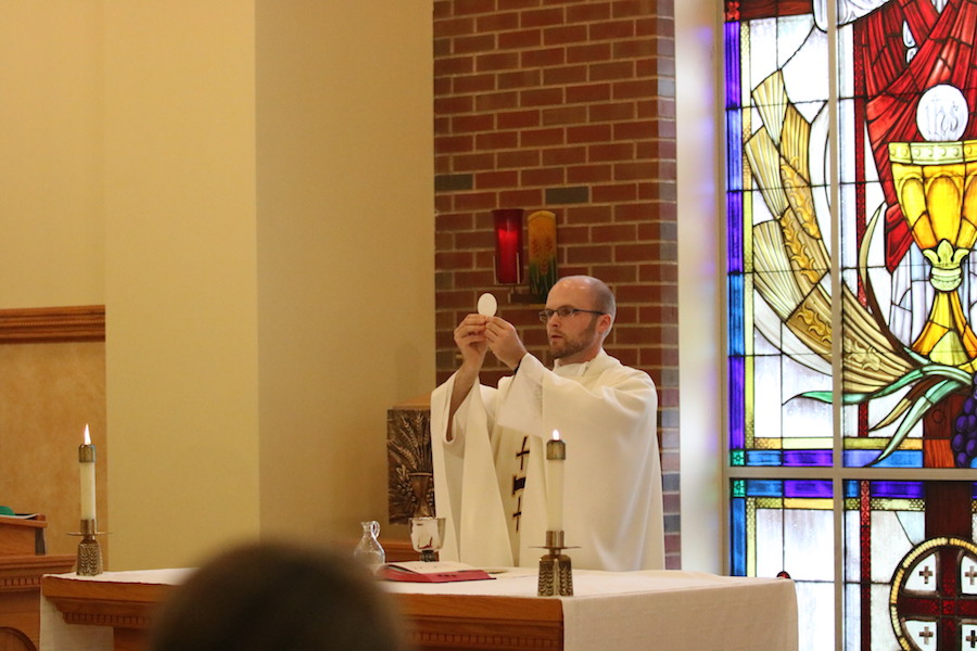 FEATURING%3A+Fr.+Dave+Marcotte+holds+the+consecrated+host+at+mass+during+fifth+period+study.+Fr.+Dave+gives+mass+during+a+study+period+most+days+of+the+week.+