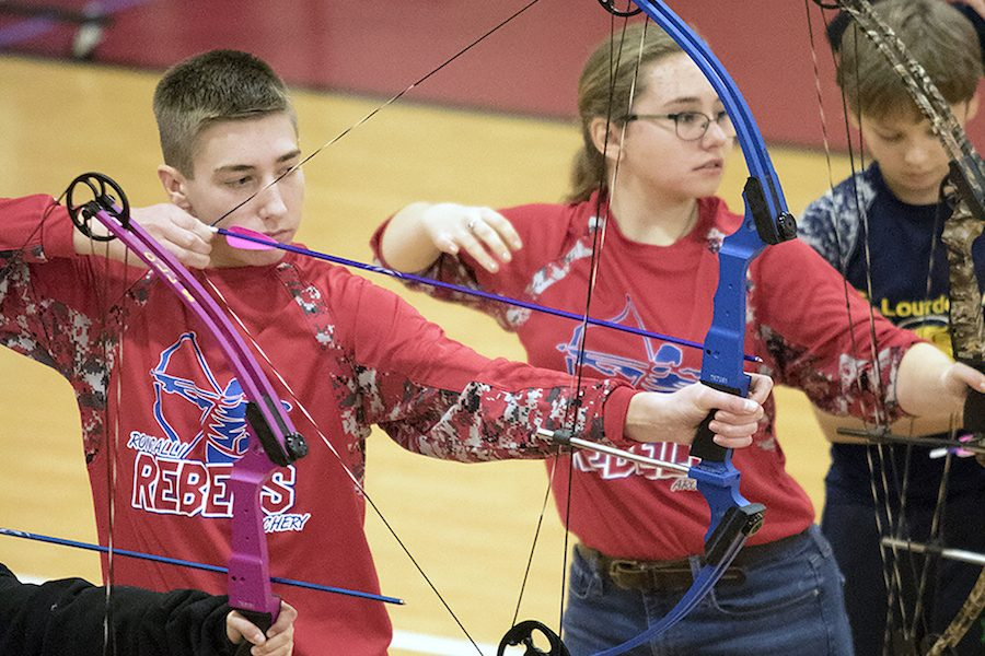 TAKING+AIM%3A+Sophomores+Elliana+Aleski+and+Blake+Prather+draw+back+their+bows+during+the+long+distance+round+of+competition.+Both+students+were+involved+in+the+formation+of+the+club+back+in+2016+and+continue+to+be+strong+performers+on+the+team.+