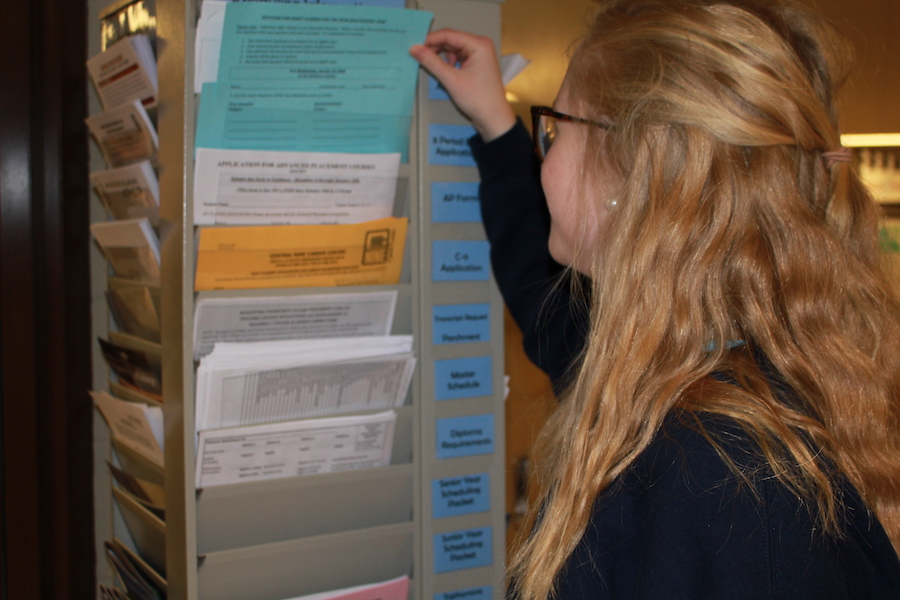 CRUISING THE CAROUSEL: Junior Isabel Elsener demonstrates where to find the scheduling information, located outside the guidance office. The carousel holds important information and applications for anything from 8-period day to scholarship applications.