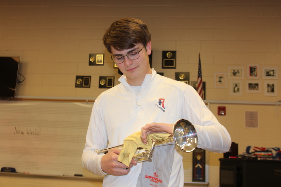 JUST LIKE NEW: Junior Henry Schutte cleans his trumpet for his next band practice. Instruments like this will be gathered from local musicians in the Indianapolis area to be refurbished.