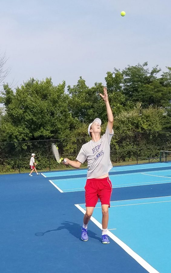 Senior Austin Schofield serves in his first match of the season. The Rebels beat the Flashes with a combined score of 3-2.