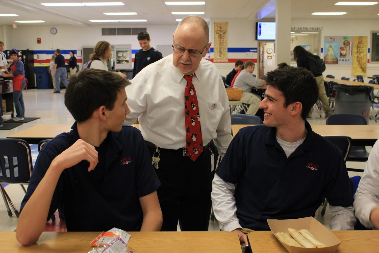FRIENDLY FACES: Mr. Bob Tully checks in on seniors Ryan Burns and Wes Cunningham during 5A lunch. Tully makes conversation with anyone and everyone that he meets.