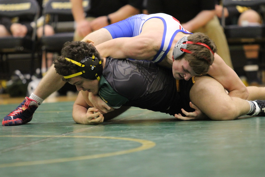 OVERPOWERING: Senior Trent Smith wrestles his opponent to the ground receiving points for a take down. Smith and other veterans are looking forward to what is looking to be a promising season.