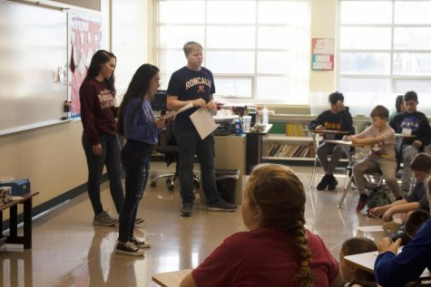 TEACHING LESSONS: Juniors Grace Plahitko and Andrew Burgan along with sophomore Chelsea Garcia teach the south deanery middle schoolers in their room about the Catholic Church. From start to finish, the youth rally was a success.