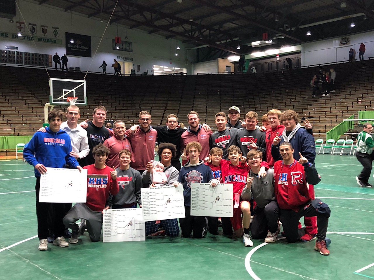 NUMBER ONE, BABY: Roncalli wrestlers celebrate their first place win. Senior Elijah Mahan holds Coach Wade McClurg's baby in celebration.