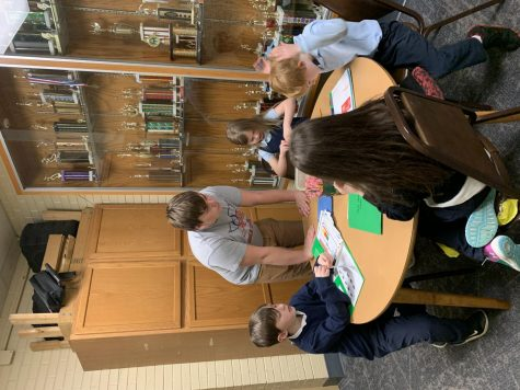 THE LION AND HIS CUBS: Junior Ben Bailey helps young students with their homework at St. Mark. This is one of his many duties that he has as a St. Mark aftercare worker.