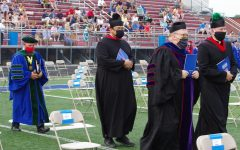 CELEBRATING THE FAITH: Father Robeson preparing to say mass at graduation for the class of 2020. Graduation was held on July 21st at the Roncalli stadium.
