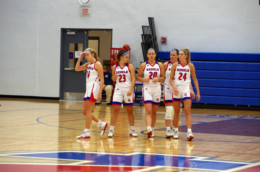 The five starters at the Roncalli vs Pike game walk out to the center of the court for tip-off.