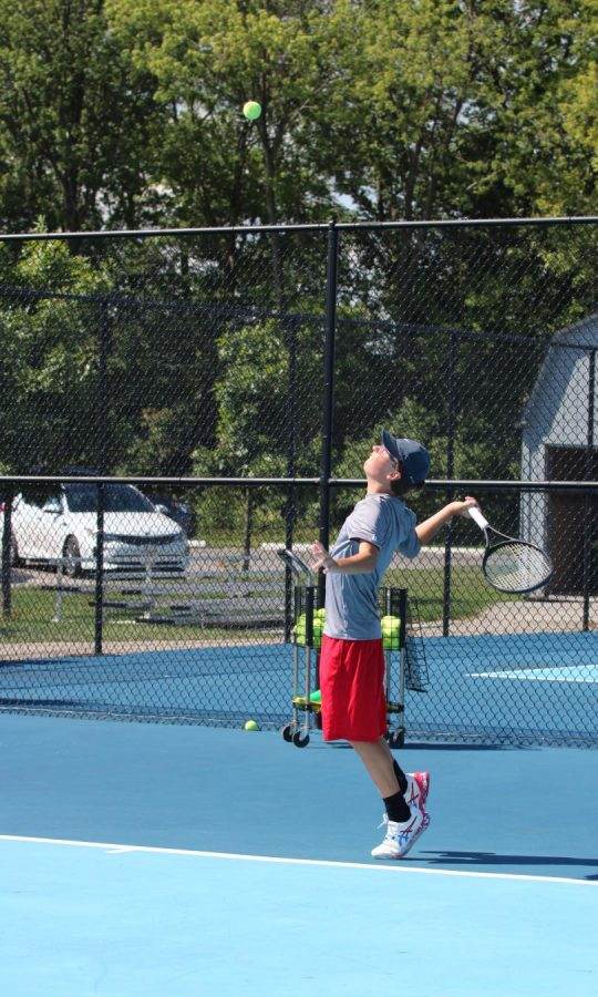 BALLS TO THE WALL: Senior Ty Ransburg prepares to slam a serve past his opponent. Ransburg, a veteran of the tennis team, will play a critical role in helping the team advance to another sectional win.