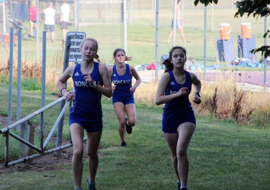 Juniors Amelia Warner and Sara McGraw run with sophomore Sophia Ramsey at a cross country meet